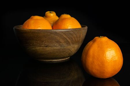 Group of four whole fresh orange tangelo minneola in big wooden bowl isolated on black glass