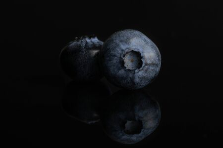 Group of two whole fresh blue bilberry isolated on black glass 写真素材