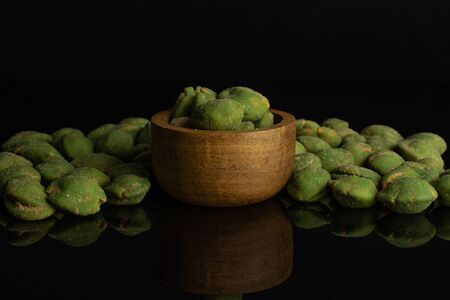 Lot of whole spicy green wasabi peanut in tiny wooden bowl isolated on black glass Stockfoto