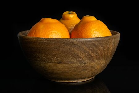 Group of three whole fresh orange tangelo minneola in big wooden bowl isolated on black glass