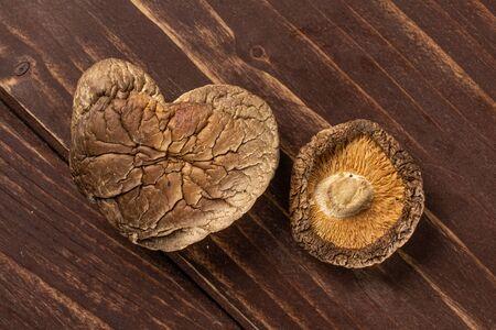 Group of two whole dry mushroom shiitake heart shape flatlay on brown wood