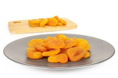 Lot of whole dried orange apricot on bamboo cutting board on gray ceramic plate isolated on white background
