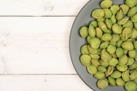 Lot of whole spicy green wasabi peanut on gray ceramic plate flatlay on white wood Stockfoto