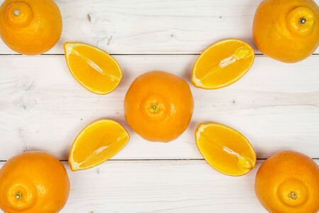 Group of five whole four quarters of fresh orange tangelo minneola flatlay on white wood Banque d'images - 129475208