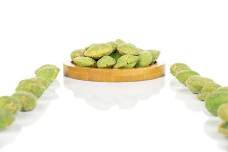 Lot of whole spicy green wasabi peanut on bamboo coaster isolated on white background Stockfoto