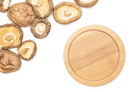 Lot of whole dry mushroom shiitake with bamboo plate flatlay isolated on white background