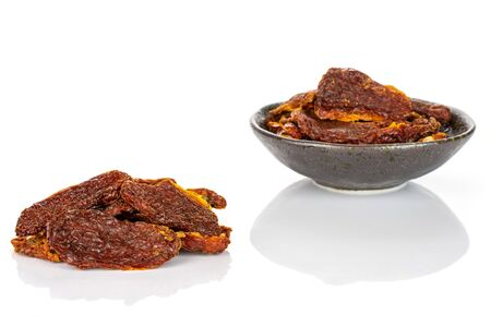 Lot of whole dried red tomato small group is in the back in dark ceramic bowl isolated on white background 写真素材