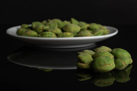 Lot of whole spicy green wasabi peanut small group is in the front and the rest is on white ceramic plate isolated on black glass