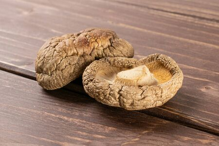 Group of two whole dry mushroom shiitake on brown wood Reklamní fotografie
