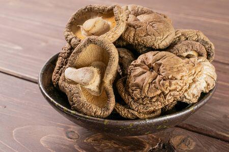 Lot of whole dry mushroom shiitake on grey ceramic plate on brown wood
