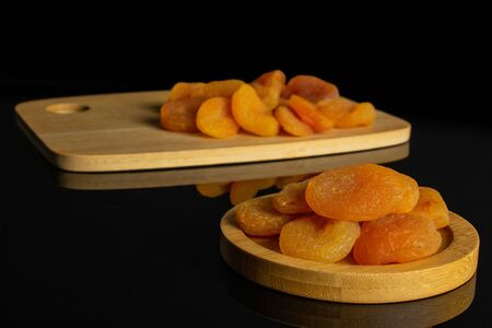Lot of whole dried orange apricot on round bamboo coaster on bamboo cutting board isolated on black glass Stock fotó
