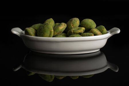 Lot of whole spicy green wasabi peanut in white oval ceramic bowl isolated on black glass Stockfoto