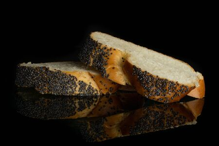 Group of two slices of fresh baked twisted poppy seed bun isolated on black glass