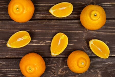 Group of four whole four quarters of fresh orange tangelo minneola flatlay on brown wood Banque d'images - 129475341
