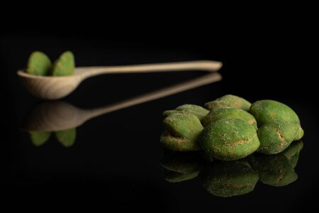 Lot of whole spicy green wasabi peanut small group is in the front and the rest is in a wooden spoon isolated on black glass
