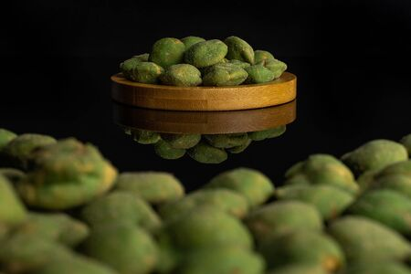 Lot of whole spicy green wasabi peanut on bamboo coaster isolated on black glass Stockfoto