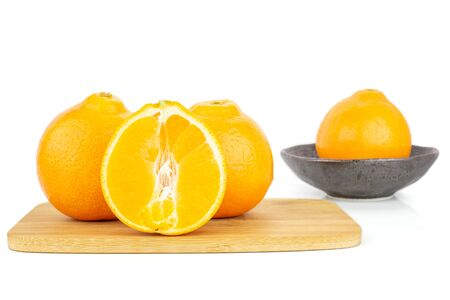 Group of three whole one half of fresh orange tangelo minneola on bamboo cutting board in dark ceramic bowl isolated on white background