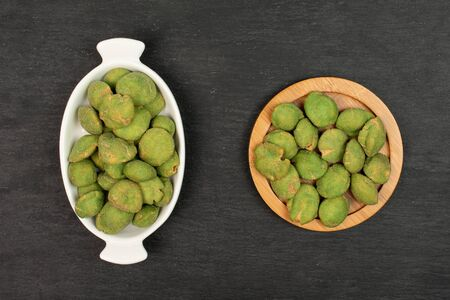 Lot of whole spicy green wasabi peanut in white oval ceramic bowl on bamboo coaster flatlay on grey stone Stockfoto