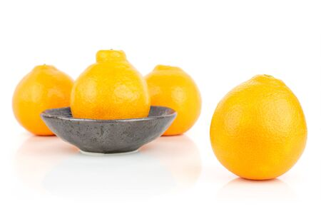 Group of four whole fresh orange tangelo minneola in dark ceramic bowl isolated on white background Banque d'images - 129475439