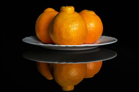 Group of three whole fresh orange tangelo minneola on white ceramic plate isolated on black glass Banque d'images - 129475459