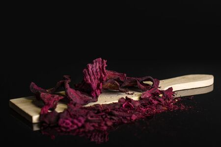 Lot of slices of dried red beetroot on small wooden cutting board isolated on black glass