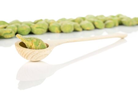 Lot of whole spicy green wasabi peanut in a wooden spoon isolated on white background