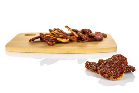 Lot of whole dried red tomato on bamboo cutting board isolated on white background Stock fotó