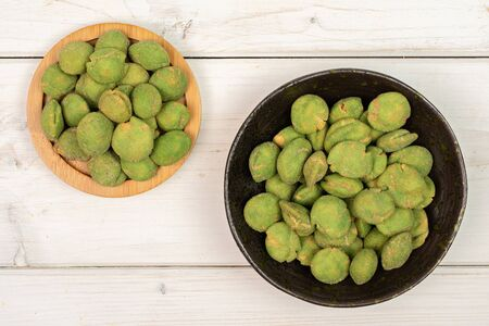 Lot of whole spicy green wasabi peanut on bamboo coaster in dark ceramic bowl flatlay on white wood