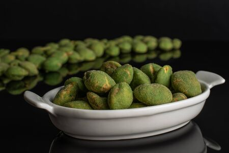 Lot of whole spicy green wasabi peanut large group is in the back and small group is in the front isolated on black glass Stockfoto