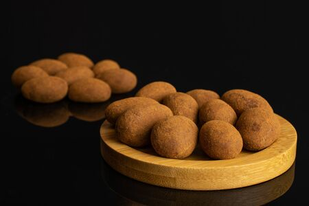 Lot of whole sweet brown chocolate cinnamon almond on round bamboo coaster isolated on black glass 写真素材