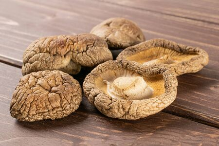 Group of five whole dry mushroom shiitake on brown wood