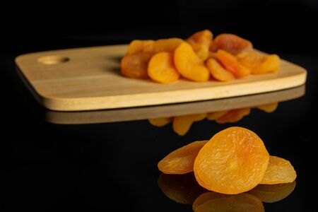 Lot of whole dried orange apricot on bamboo cutting board isolated on black glass