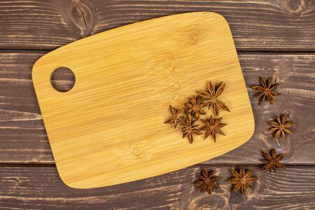 Lot of whole dry brown star anise illicium verum on bamboo cutting board flatlay on brown wood