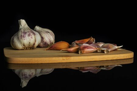 Group of two whole lot of pieces of organic white garlic allium sativum on bamboo cutting board isolated on black glass Stock fotó