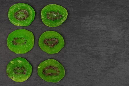 Group of six slices of sweet green candied kiwifruit flatlay on grey stone Banco de Imagens