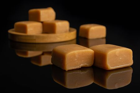 Group of six whole sweet golden caramel candy on bamboo coaster isolated on black glass