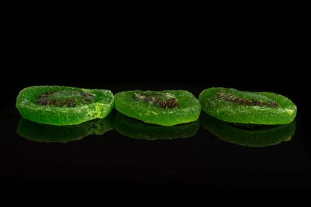 Group of three slices of sweet green candied kiwifruit isolated on black glass Banco de Imagens