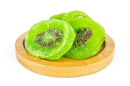 Group of four slices of sweet green candied kiwifruit on bamboo coaster isolated on white background Banco de Imagens
