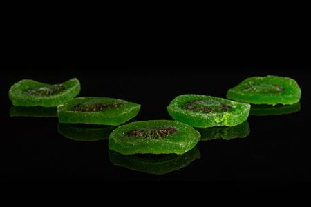 Group of five slices of sweet green candied kiwifruit isolated on black glass