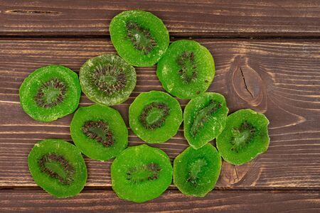 Lot of slices of sweet green candied kiwifruit flatlay on brown wood