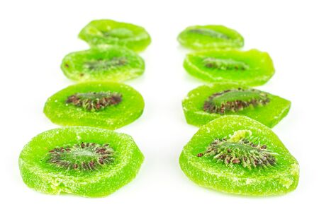 Group of eight slices of sweet green candied kiwifruit isolated on white background