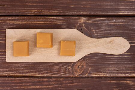 Group of three whole sweet golden caramel candy on small wooden cutting board flatlay on brown wood 写真素材