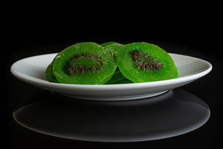 Group of three slices of sweet green candied kiwifruit on white ceramic plate isolated on black glass