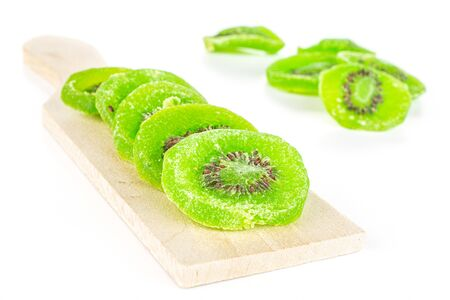 Lot of slices of sweet green candied kiwifruit on small wooden cutting board isolated on white background Banco de Imagens