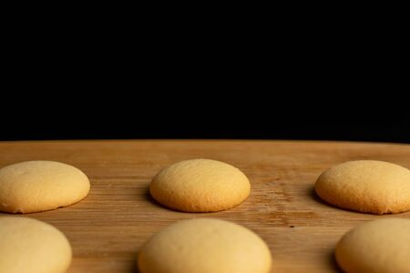 Group of six whole sweet golden sponge biscuit on bamboo cutting board isolated on black glass