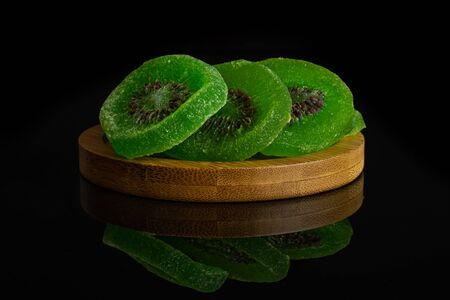 Group of three slices of sweet green candied kiwifruit on bamboo coaster isolated on black glass