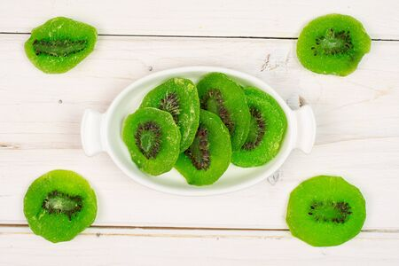 Group of nine slices of sweet green candied kiwifruit in white oval ceramic bowl flatlay on white wood Banco de Imagens