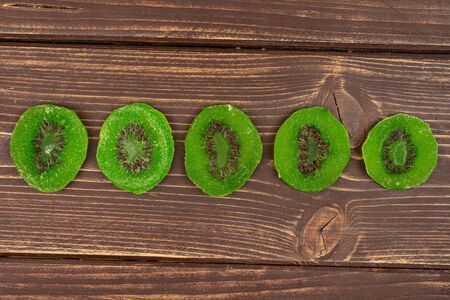 Group of five slices of sweet green candied kiwifruit flatlay on brown wood Banco de Imagens