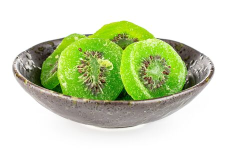 Lot of slices of sweet green candied kiwifruit in dark ceramic bowl isolated on white background