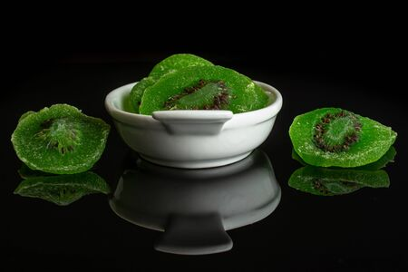 Lot of slices of sweet green candied kiwifruit in white oval ceramic bowl isolated on black glass